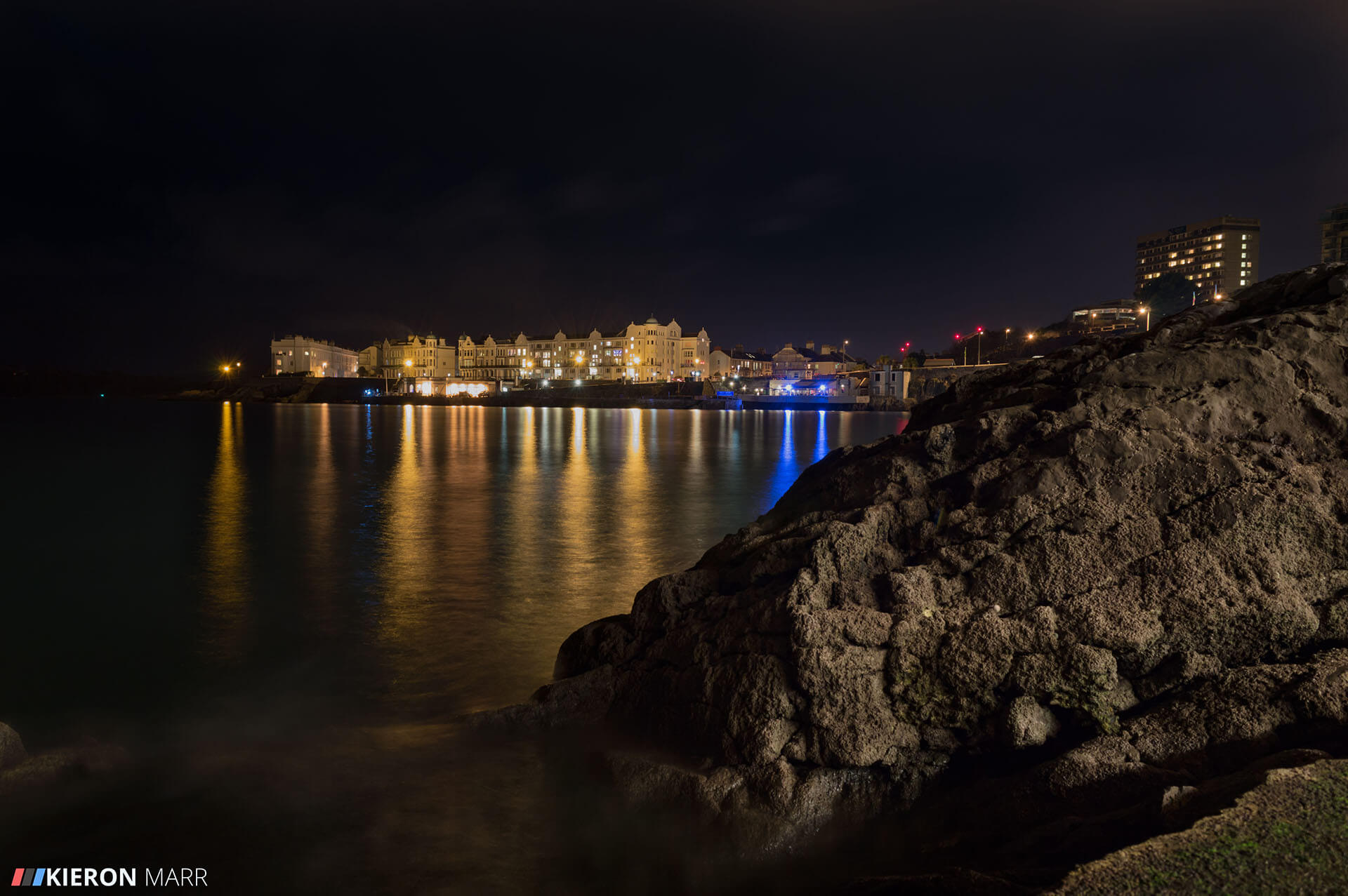 Plymouth Hoe at night with the lights reflecting off the water